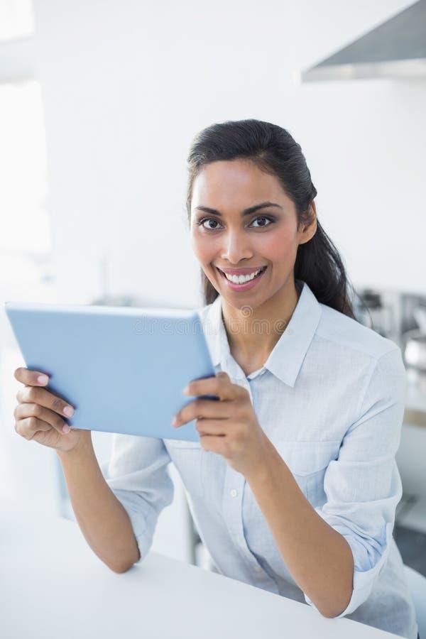 Donna pacifica attraente che tiene la sua compressa che sorride allegramente alla macchina fotografica immagine stock libera da diritti