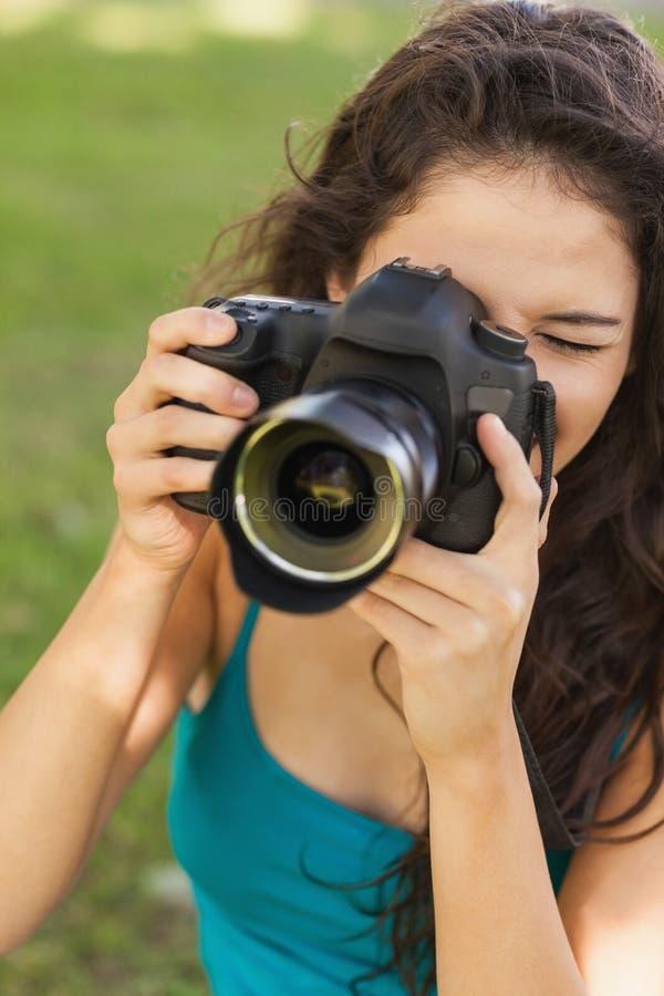 Donna pacifica splendida che usando la sua macchina fotografica fotografie stock libere da diritti