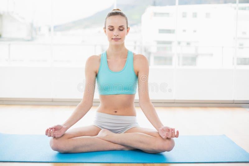 Donna pacifica sportiva che si siede a gambe accavallate sulla stuoia di esercizio fotografie stock