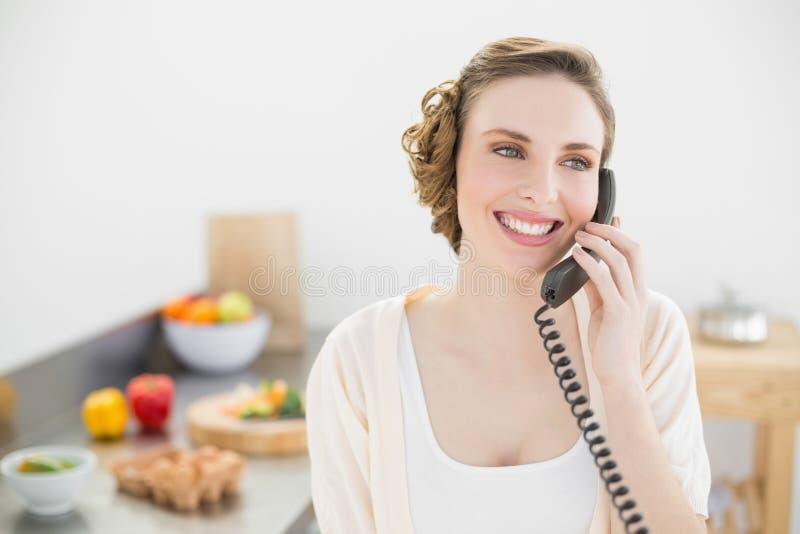 Donna pacifica sveglia che telefona con un telefono nella sua cucina fotografie stock libere da diritti