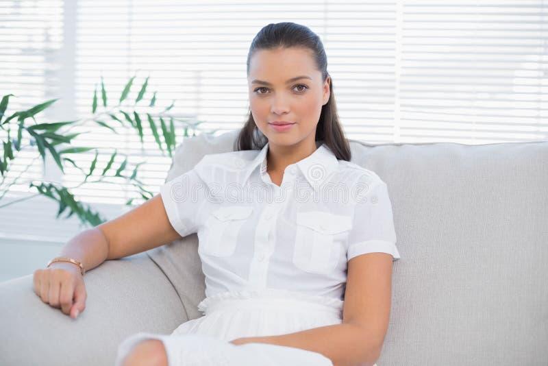 Donna pacifica in vestito bianco che si siede sul sofà fotografia stock