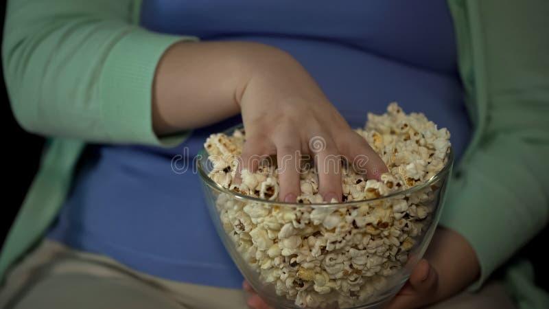 Donna paffuta che prende manciata di popcorn grasso, stile di vita sedentario, sovrappeso fotografia stock libera da diritti