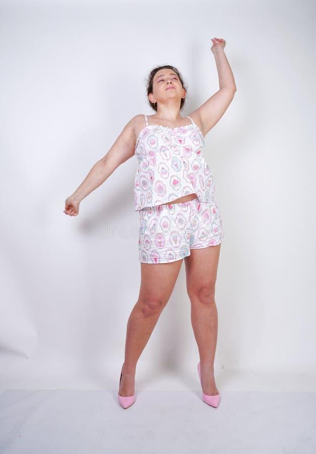 Donna paffuta Curvy nei supporti divertenti dei pigiami e stretchintg su un fondo bianco nello studio fotografie stock