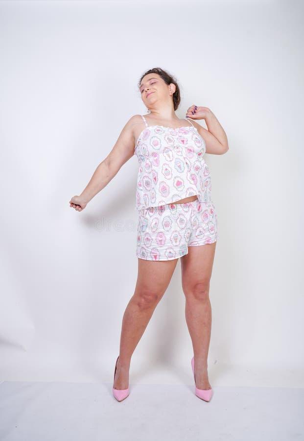 Donna paffuta Curvy nei supporti divertenti dei pigiami e stretchintg su un fondo bianco nello studio immagini stock libere da diritti