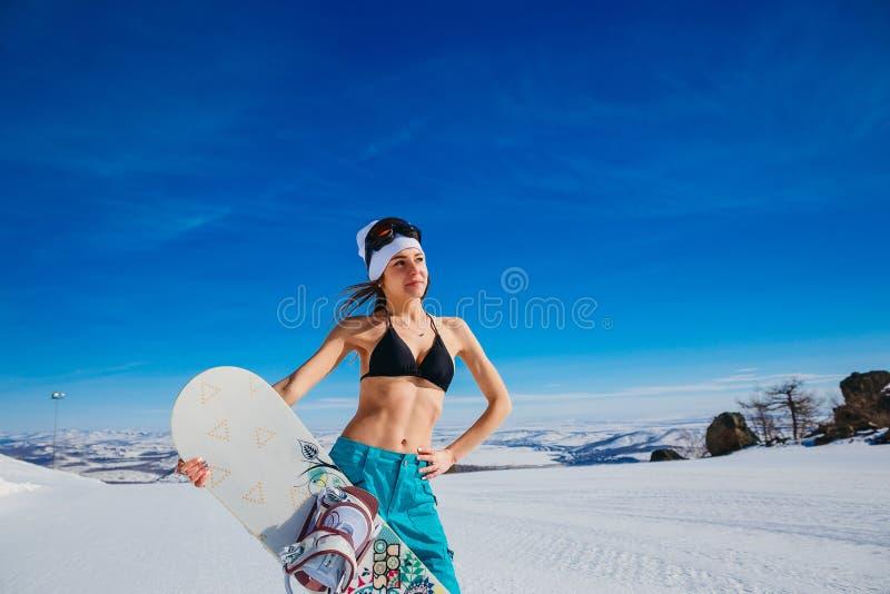 Donna in pantaloni di Bologna di inverno e del costume da bagno con lo snowboard a disposizione nell'inverno nelle montagne fotografia stock libera da diritti