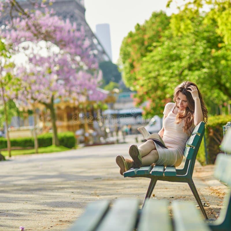 Donna a Parigi, leggente un libro vicino alla torre Eiffel fotografie stock