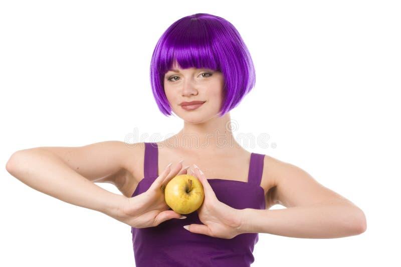 Donna in parrucca con la mela gialla fotografie stock libere da diritti