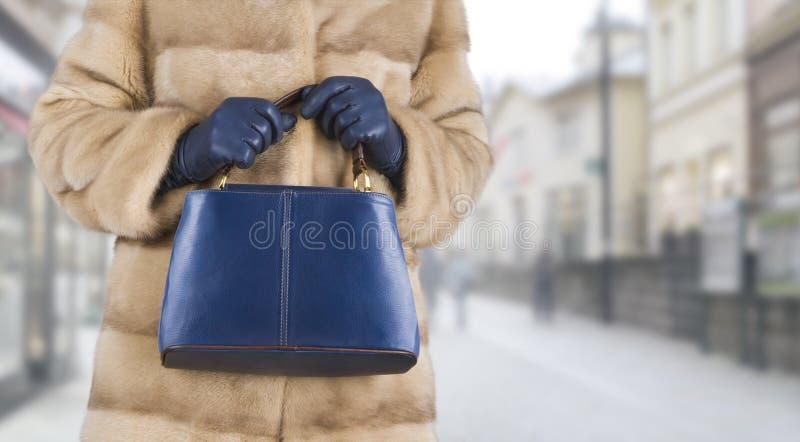 Donna in pelliccia del visone che tiene borsa di cuoio in mani fotografia stock libera da diritti