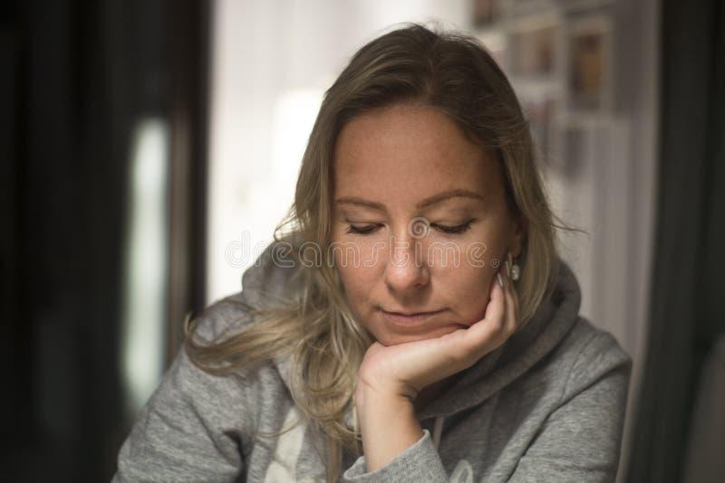 Donna pensierosa a casa, sedendosi sulla sedia fotografie stock libere da diritti