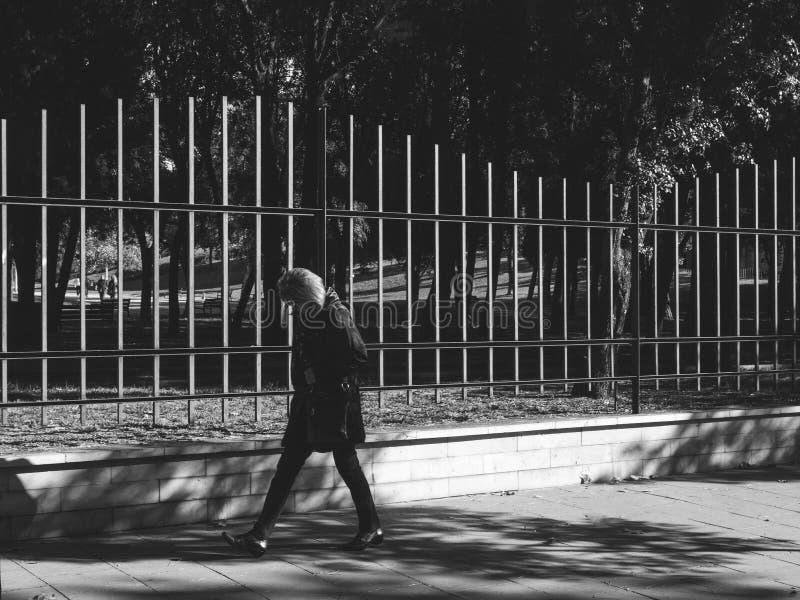 Donna pensierosa che cammina vicino al Parc de la Ciutadella protettivo fotografia stock