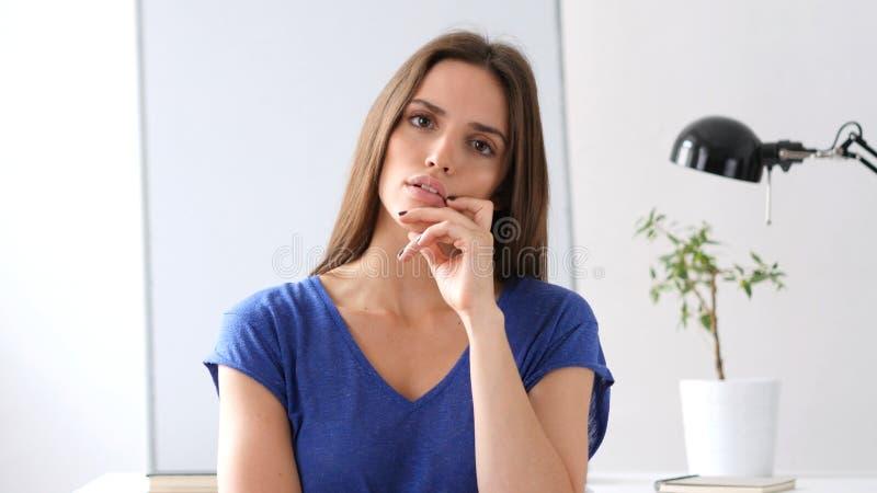 Donna pensierosa che guarda in camera, perso nei pensieri fotografie stock libere da diritti