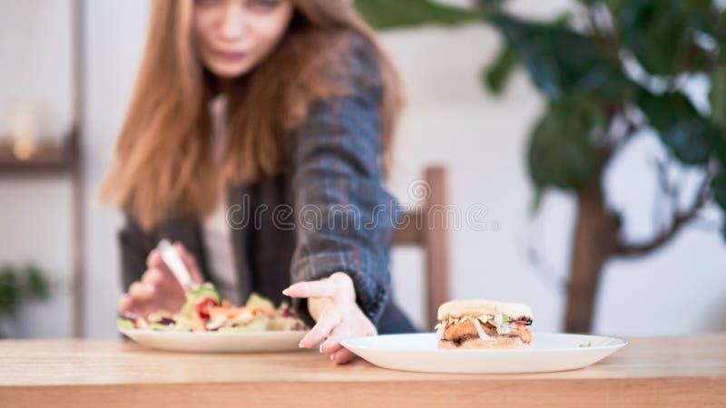 Donna pensierosa che prende decisione fra alimento sano ed alimenti a rapida preparazione Concetto sano di cibo Donna di affari i fotografia stock