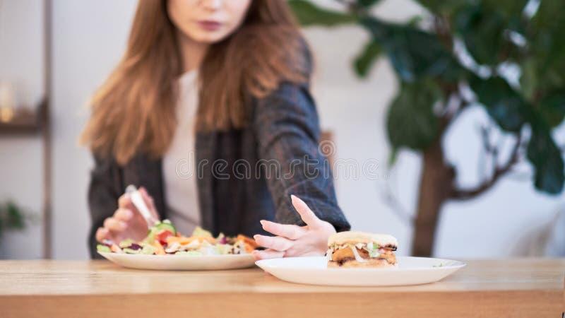 Donna pensierosa che prende decisione fra alimento sano ed alimenti a rapida preparazione Concetto sano di cibo Donna di affari i fotografia stock libera da diritti