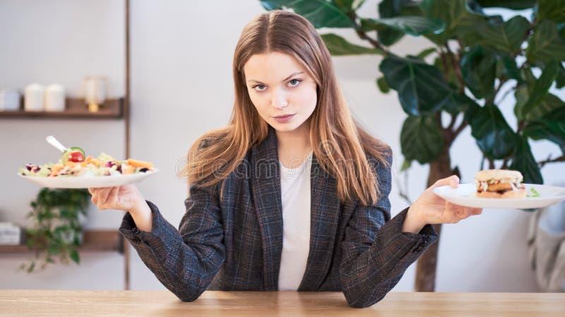 Donna pensierosa che prende decisione fra alimento sano ed alimenti a rapida preparazione Concetto sano di cibo Donna di affari i immagini stock