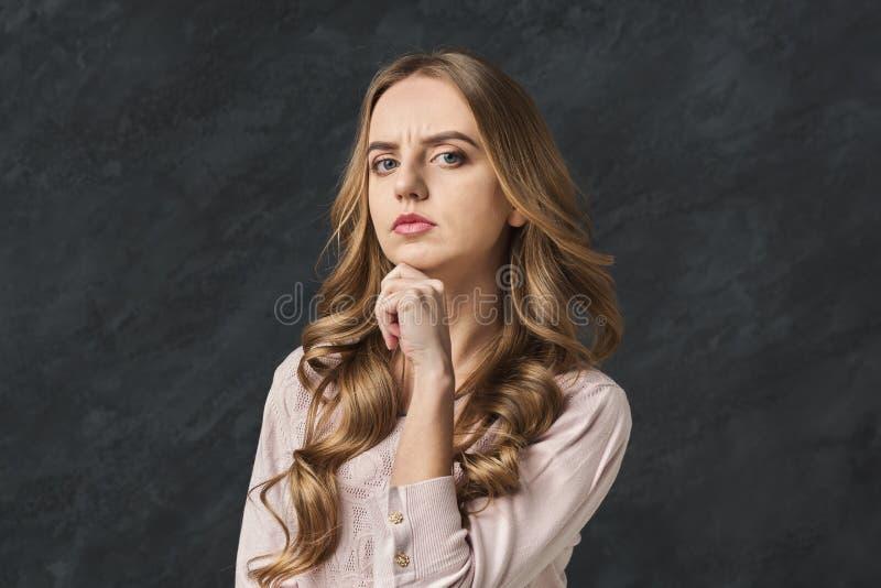 Donna pensierosa che tocca il suo mento, spazio della copia immagini stock