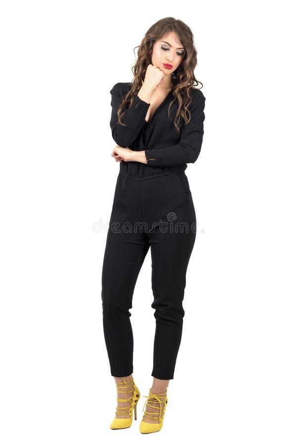 Donna pensierosa con la testa che riposa sulla sua mano che guarda giù immagini stock