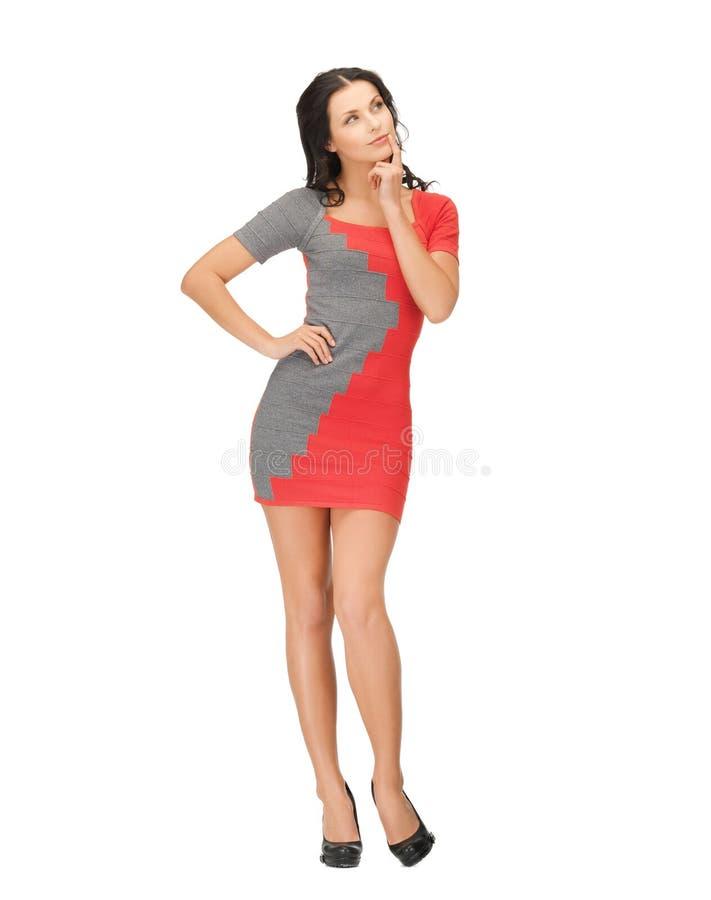 Donna pensierosa in vestito rosso fotografia stock