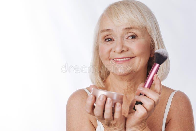 Donna pensionata allegra che fa facendo uso della cipria immagini stock libere da diritti