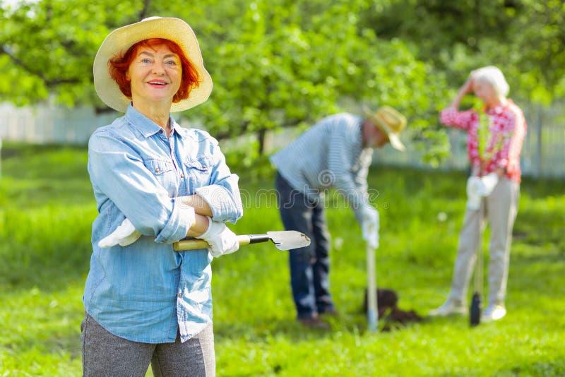 Donna pensionata allegra con le labbra luminose che ritengono felici prendendo cura del giardino immagine stock