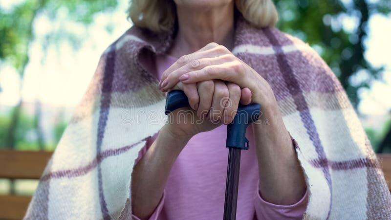 Donna pensionata malato che si siede sul banco che si appoggia bastone da passeggio, stile di vita di pensione fotografia stock libera da diritti