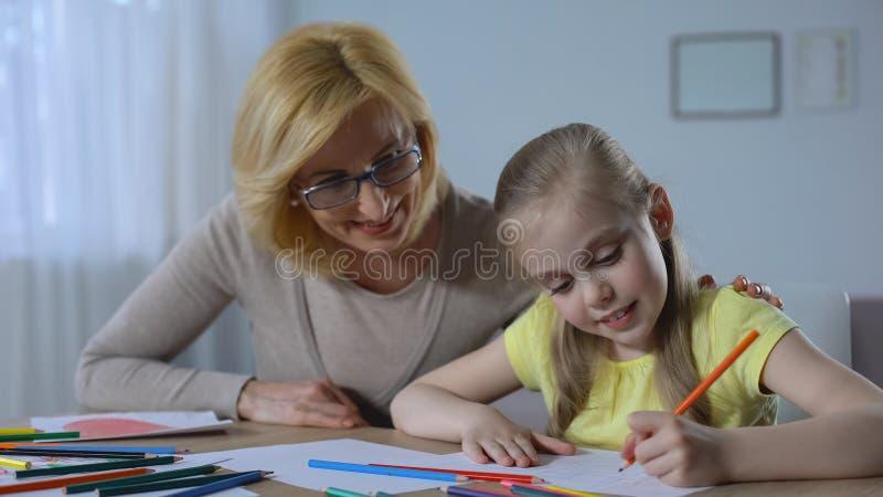 Donna pensionata preoccupantesi che esamina la pittura sveglia della nipote con le matite colorate fotografie stock libere da diritti