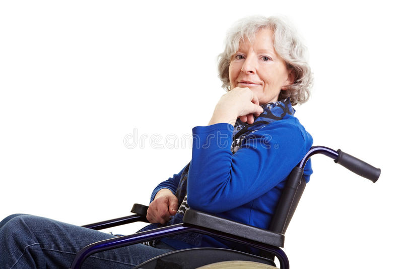 Donna pensionata sorridente in sedia a rotelle fotografia stock