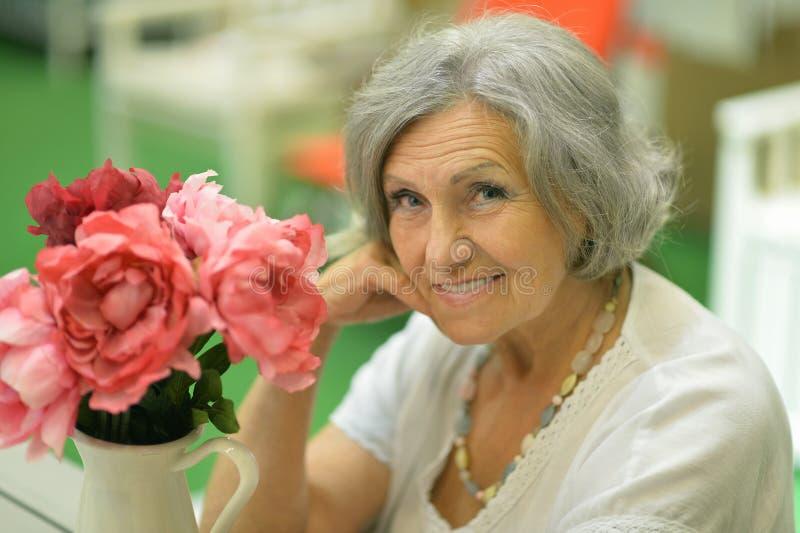 Donna pensionata sveglia con i fiori fotografia stock