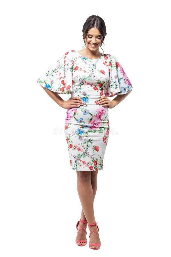 Donna perfetta del modello di moda con le mani sulle anche che sorride e che guarda giù fotografia stock