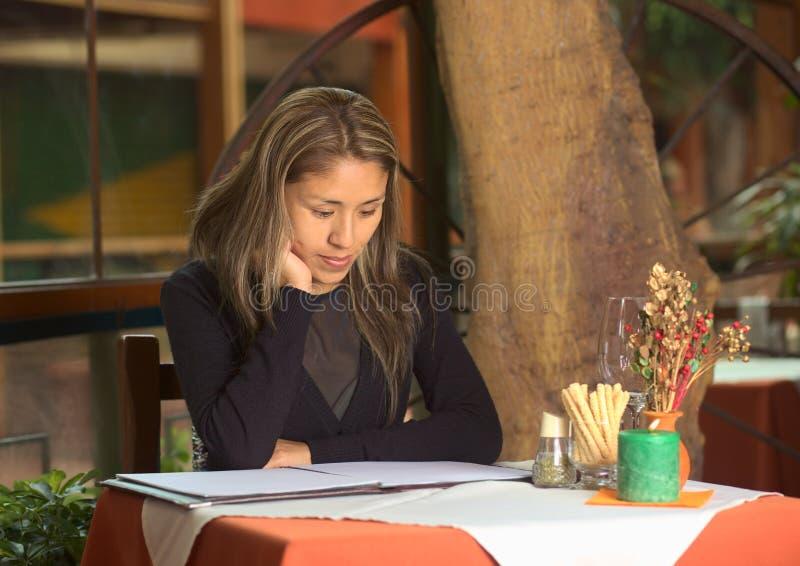 Donna peruviana che esamina il menu in un ristorante immagini stock