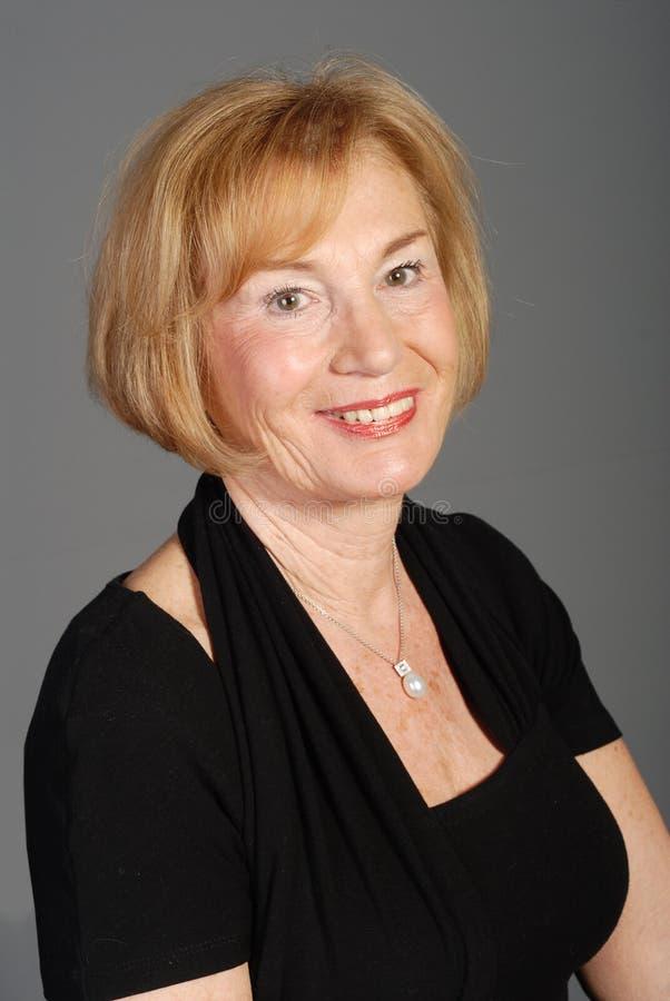 Donna più anziana attraente in vestito nero immagini stock