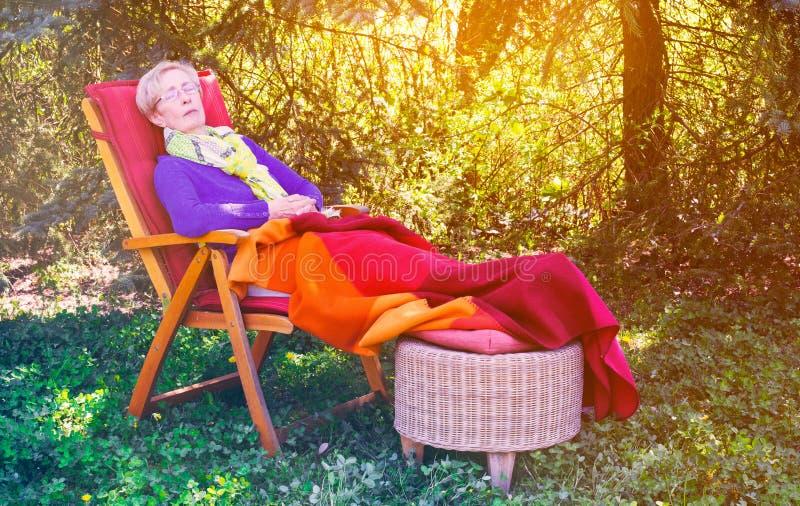Donna più anziana che dorme nella sedia nel giardino immagine stock
