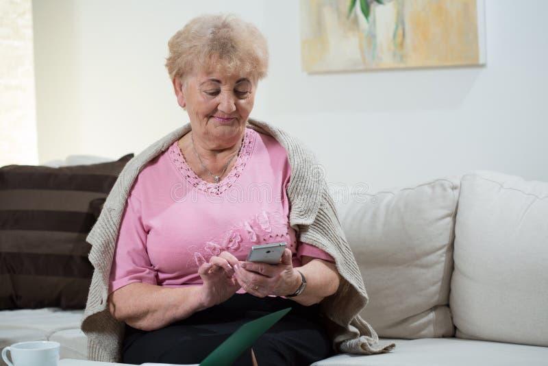 Donna più anziana che per mezzo del telefono cellulare immagine stock libera da diritti