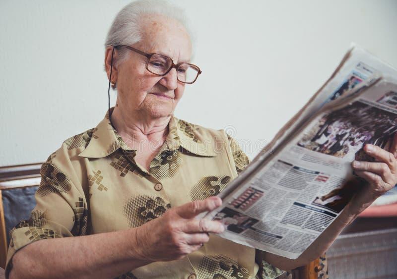 Donna più anziana che si rilassa e che legge giornale fotografie stock