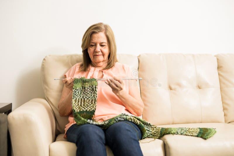 Donna più anziana che tricotta una sciarpa a casa immagine stock