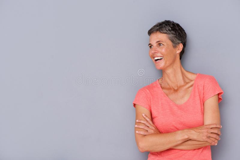 Donna più anziana di risata contro la parete grigia fotografie stock libere da diritti