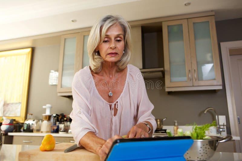 Donna più anziana dopo la ricetta in cucina sulla compressa immagini stock libere da diritti