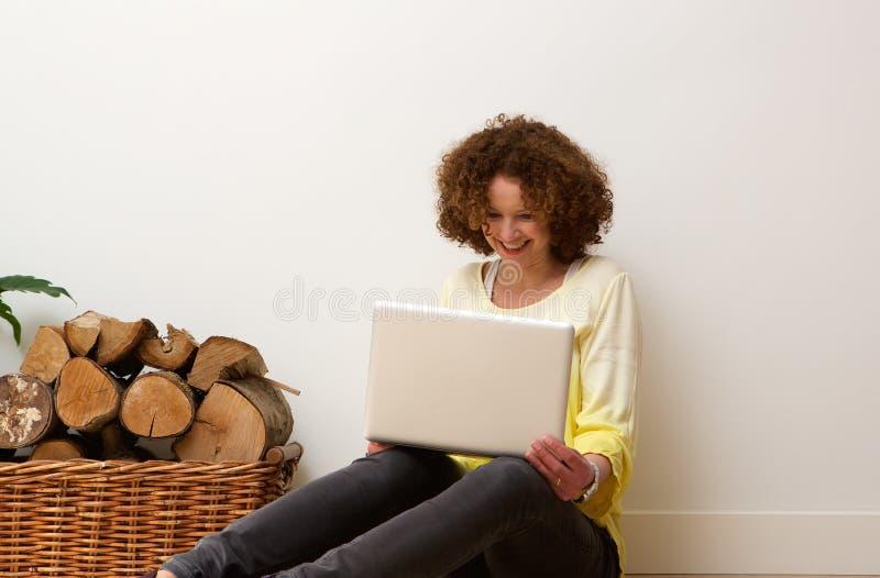 Donna più anziana felice che usando la casa dell'avena del computer portatile immagini stock libere da diritti