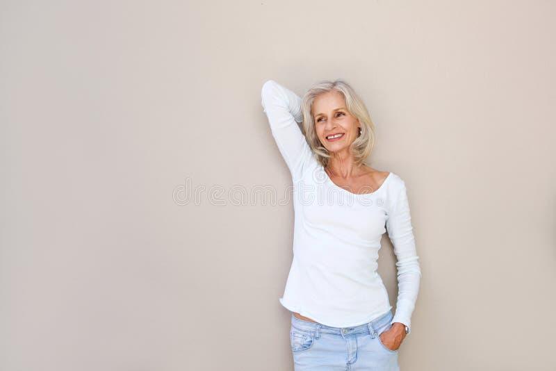 Donna più anziana felice spensierata con la mano da dirigersi immagine stock libera da diritti