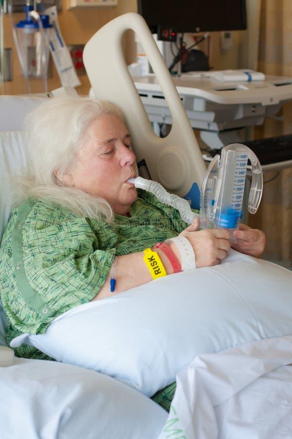 Donna più anziana nel letto di ospedale facendo uso dello spirometro incentivo immagine stock libera da diritti