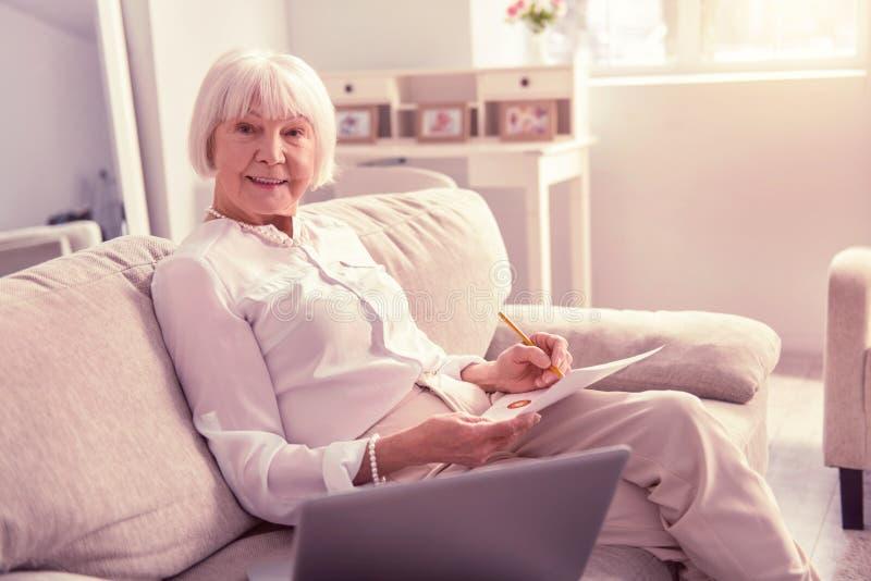 Donna più anziana piacevole positiva che tiene una matita fotografie stock libere da diritti