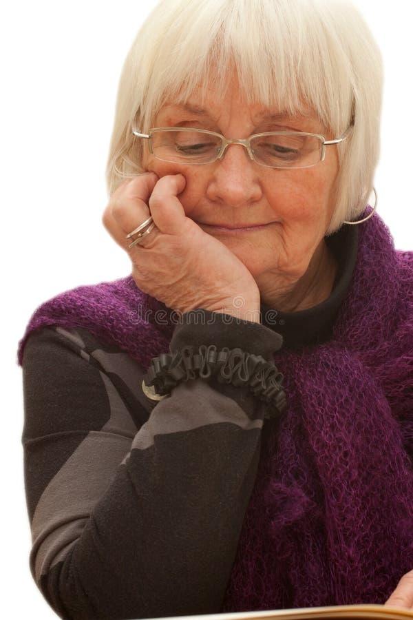 Donna più anziana premurosa che legge un libro fotografia stock