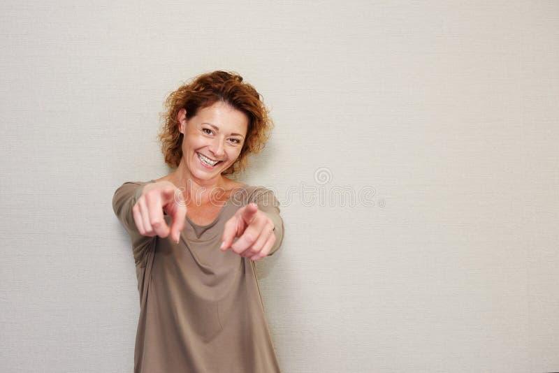 Donna più anziana sorridente che indica le dita fotografia stock