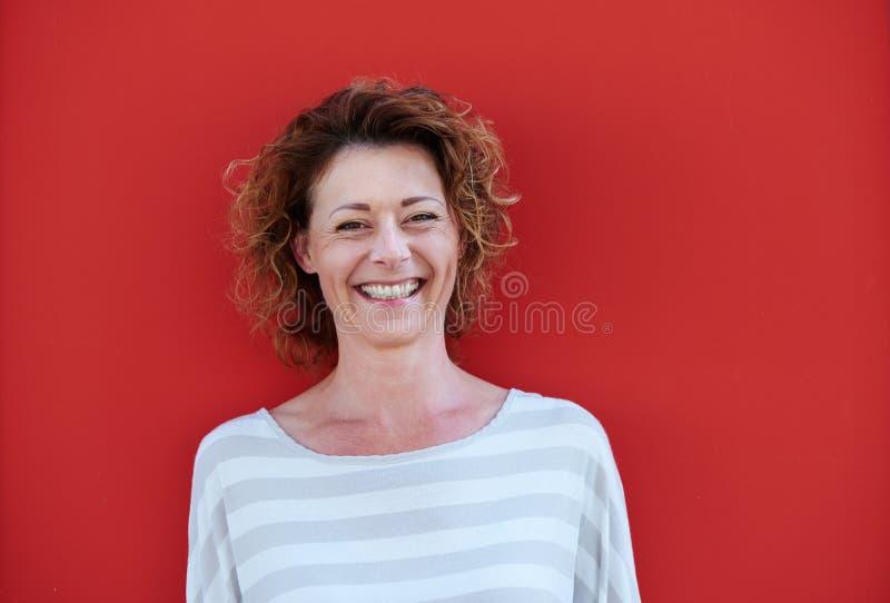 Donna più anziana sorridente con capelli ricci contro la parete rossa fotografia stock