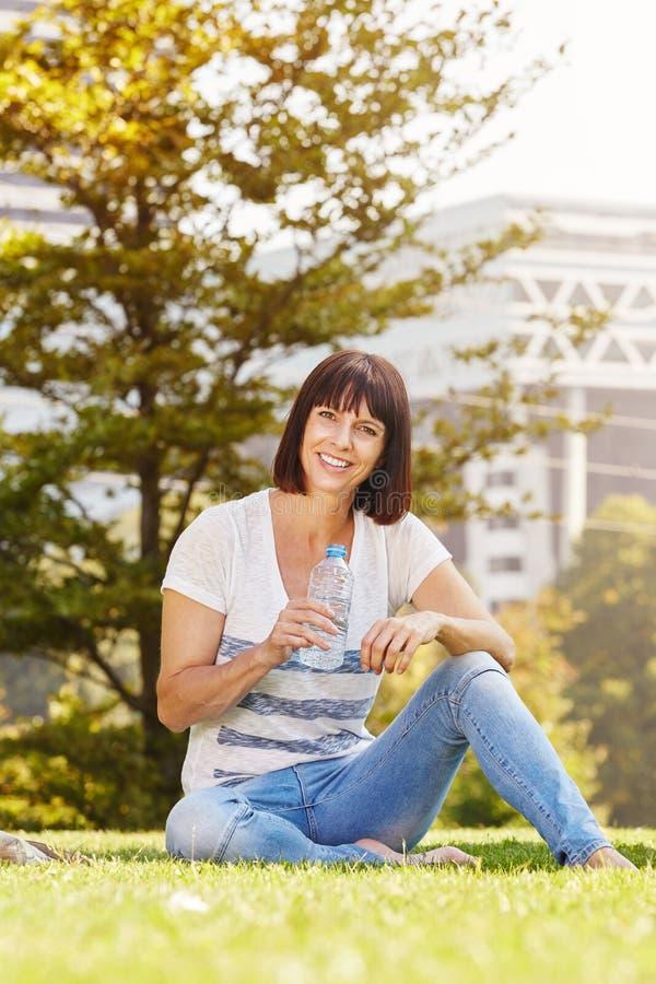 Donna più anziana sorridente con la bottiglia di acqua che si siede nell'erba fotografie stock