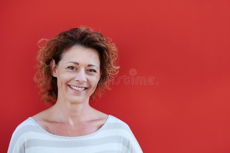 Donna più anziana sorridente contro fondo rosso fotografia stock