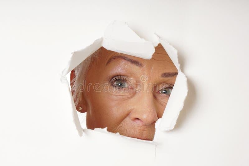 Donna più anziana vigile che guarda attraverso il foro fotografia stock