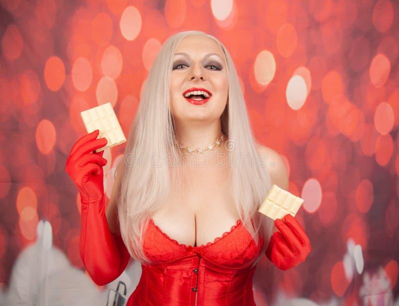 Donna più bionda sessuale di dimensione con l'ente paffuto che porta biancheria rossa con i pezzi delle tenute e del corsetto di  immagine stock libera da diritti