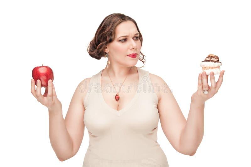 Donna più di dimensione che opera scelta fra la mela e la pasticceria fotografie stock libere da diritti
