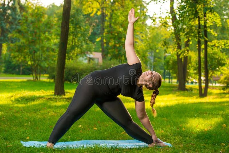 donna più flessibile di dimensione che fa ginnastica fotografia stock