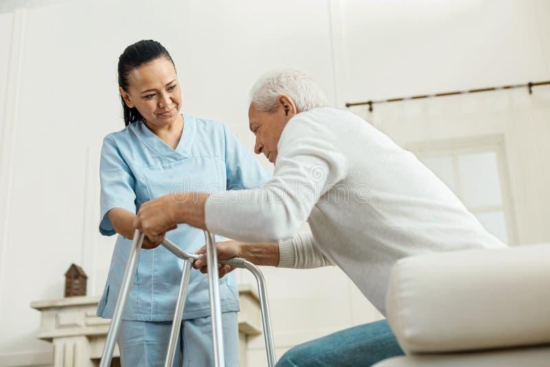 Donna piacevole allegra che aiuta un uomo anziano immagini stock